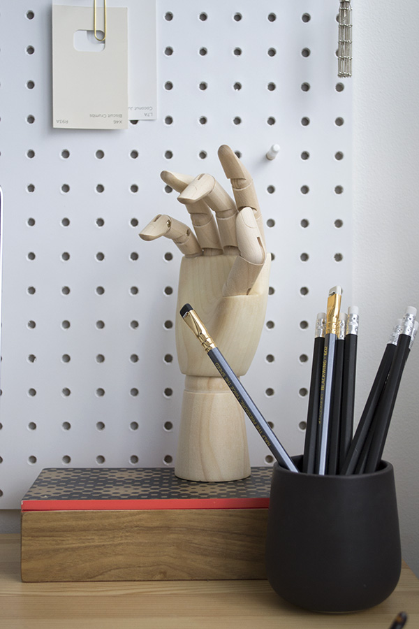 Minimal workspace featuring white Pegboard from Block and HAY wooden hand