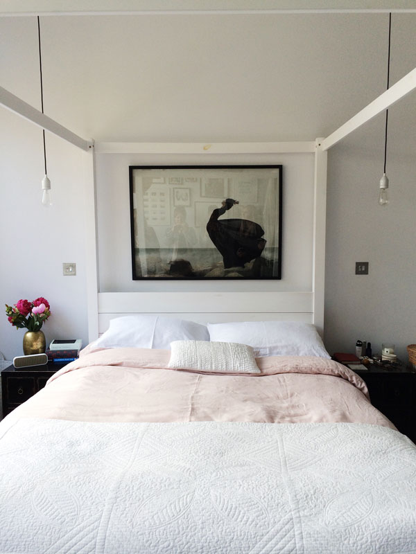 White four poster bed inside monochrome loft apartment in Hackney