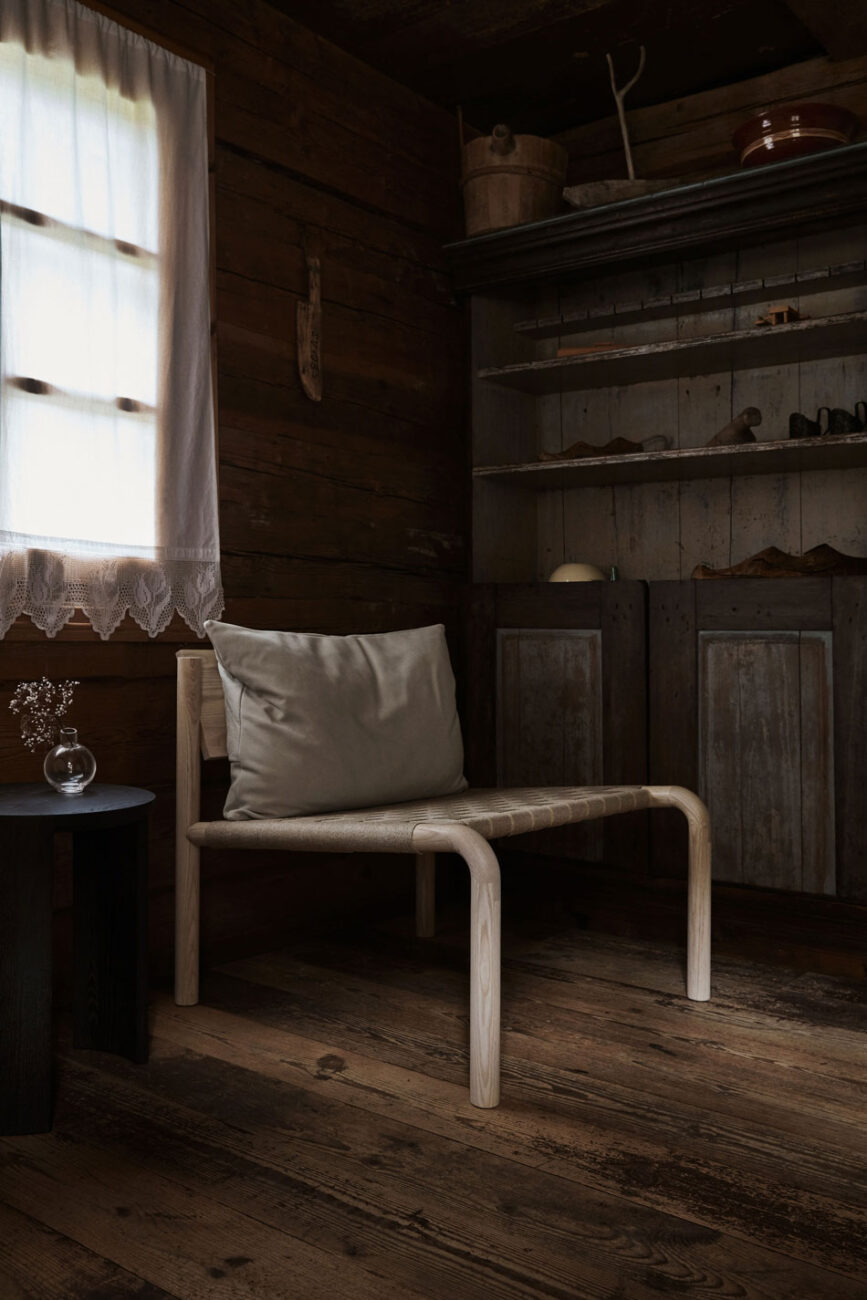 The Made By Choice Kaski linen lounge chair styled inside a traditional rustic Finnish wood cabin in the countryside.